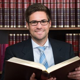 Young male attorney bookshelf